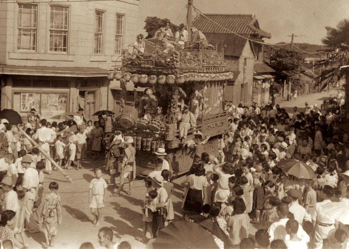 昭和22年の館山祭礼。たくさんの観衆に囲まれている下町の山車(下町角・福島屋前)。