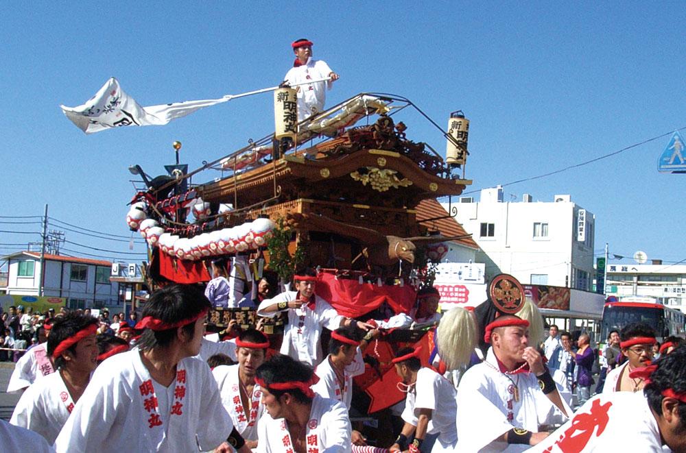 紅で描かれた「あらい」の半纏を纏った若衆の威勢の良い曳き廻し